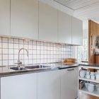 Кухня, как это часто бывает в скандинавских домах, нейтрально белая с простым белым кафелем.