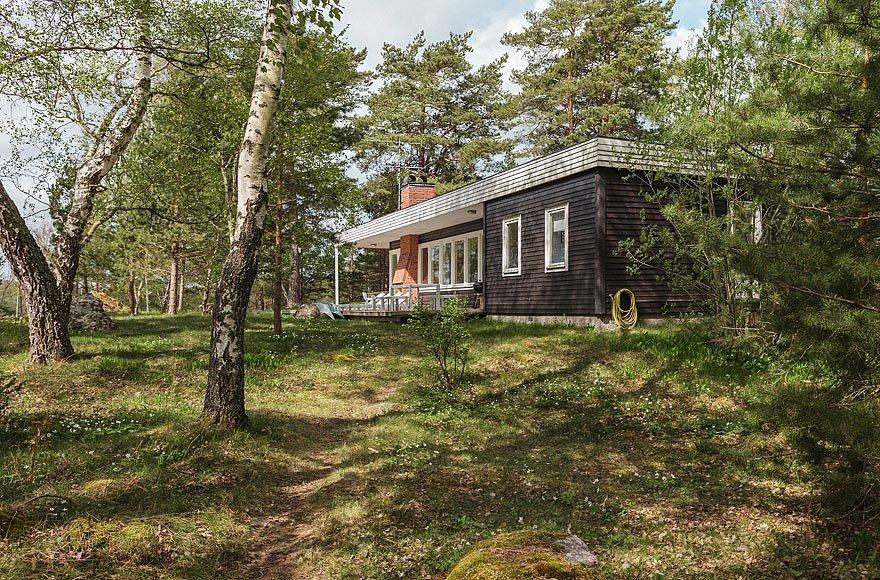Одноэтажный черный домик великолепно вписывается в лесной пейзаж.