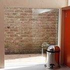 Окно на уровне пола улучшает освещенность комнаты и кирпичная стена привносит необычную кирпичную текстуру в фанерный интерьер гостевого домика.