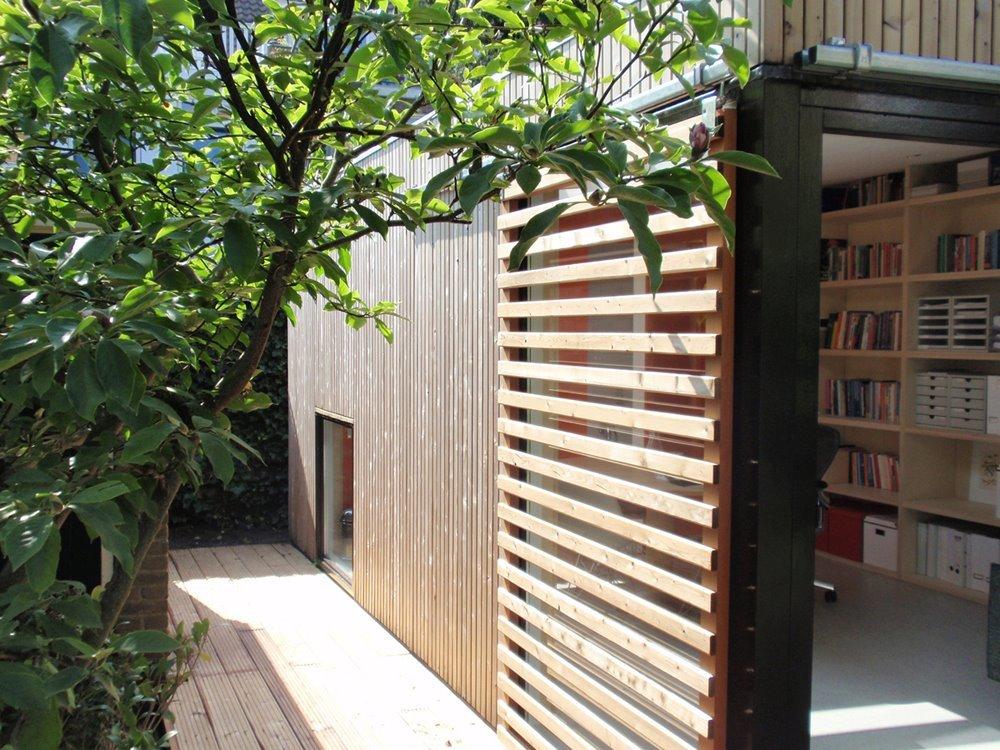Снаружи домик обшит деревом. Внутри фанерой. Целая стена занята книжными полками.