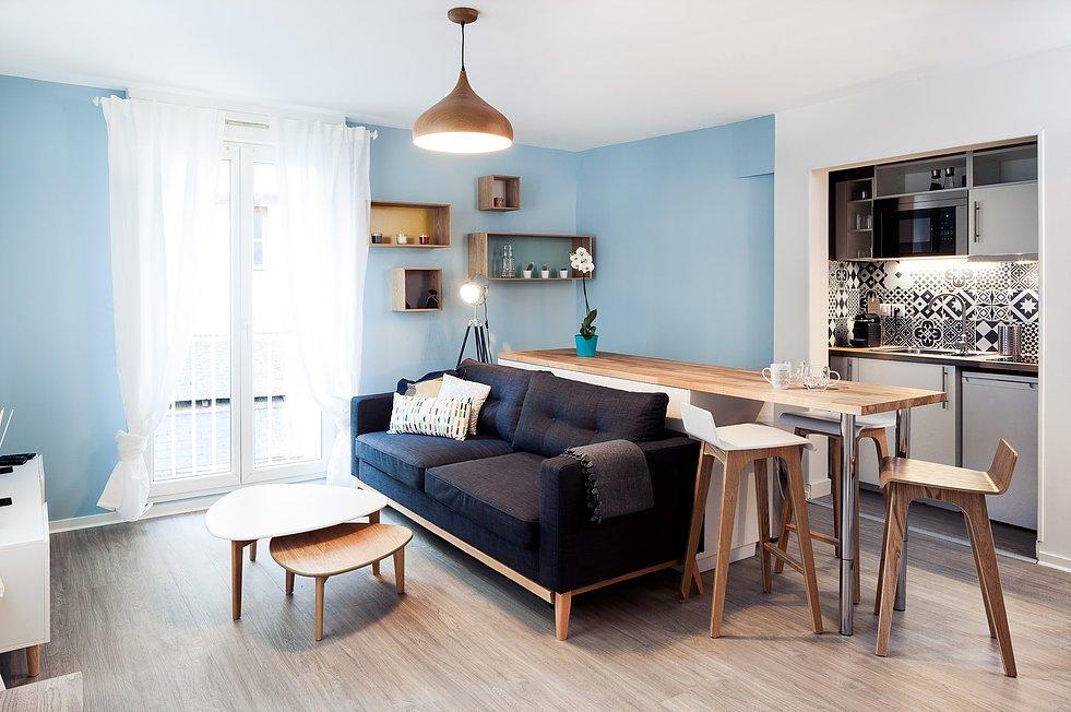 Поскольку кухня в нише очень маленькая, то кухонный остров вынесен в гостиную. Диван расположен в непосредственной близости от кухонного острова.