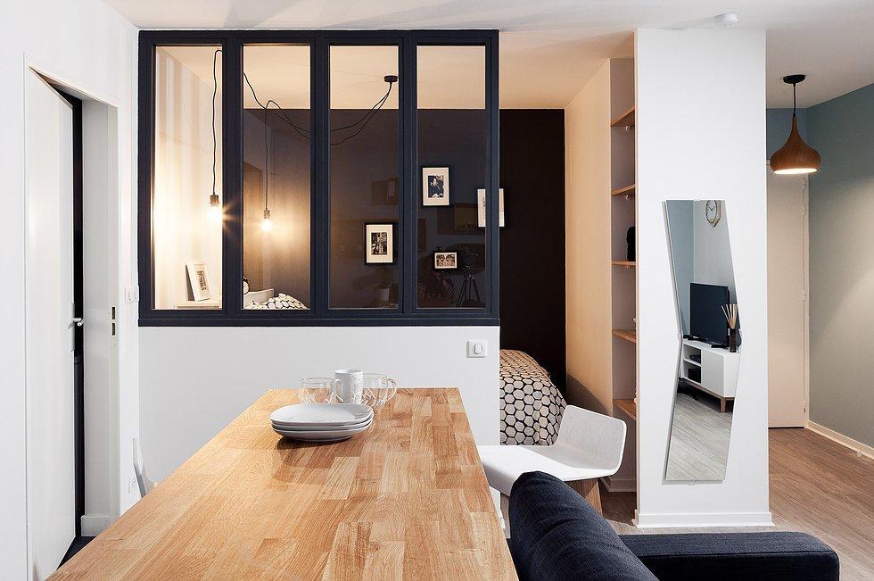 Стеклянная перегородка между гостиной и спальней позволяет улучшить инсоляцию последней. Ведь спальня не имеет собственных окон