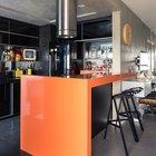 Оранжевая барная стойка очень оживляет серый интерьер. Мелкий черный кафель выделяет кухню и придает небольшому помещению объема.