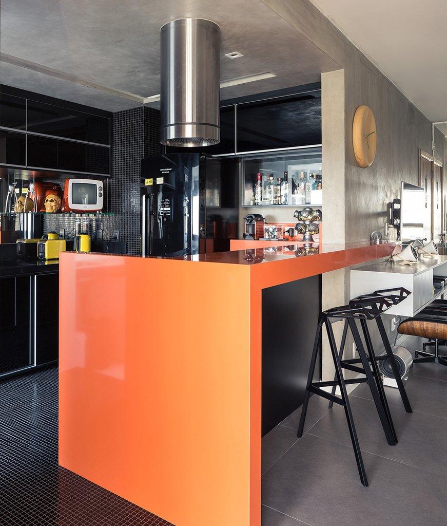 Оранжевая барная стойка очень оживляет серый интерьер. Мелкий черный кафель выделяет кухню и придает небольшому помещению объема