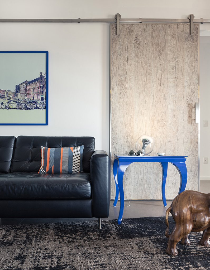 Сдвижные двери из выбеленной древесины как нельзя лучше подходят мужественному интерьеру квартиры