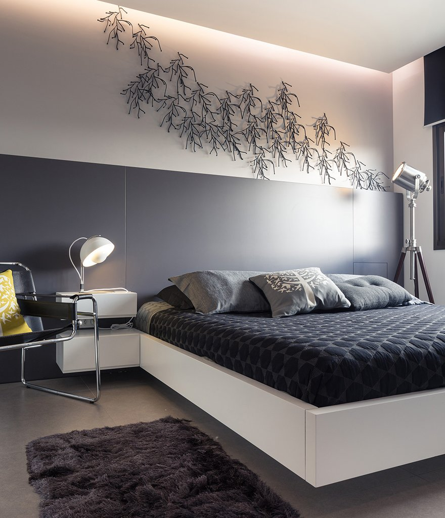 Серое изголовье кровати распространяется на всю стену, ножки кровати скрыты от взора.