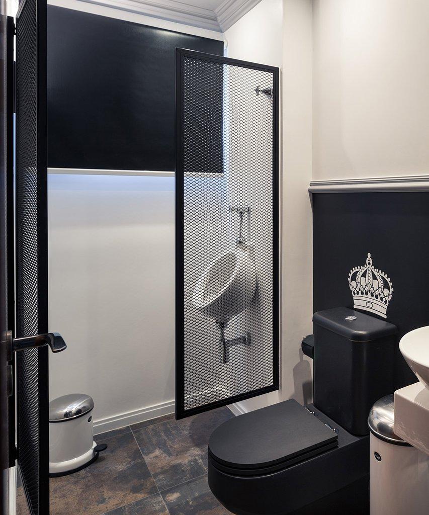 Ванная комната в черно-белых тонах с королевским черным унитазом и выделенный стальными решетчатыми воротами писсуар.