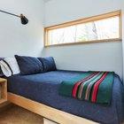 Спальня, как можно ожидать от маленького дома, содержит только самое необходимое. Однако тут можно найти полноценную большую кровать. Расположенное высоко окно дает много света и не нарушает приватности.