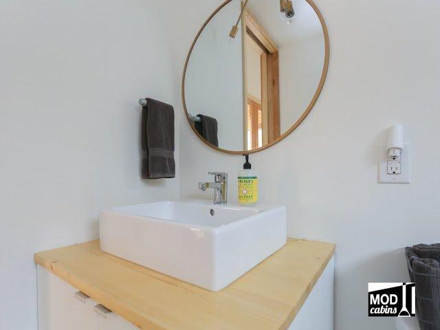 Круглое зеркало и небольшой умывальник на деревянной столешнице. Вокруг умывальника достаточно места для всего необходимого.