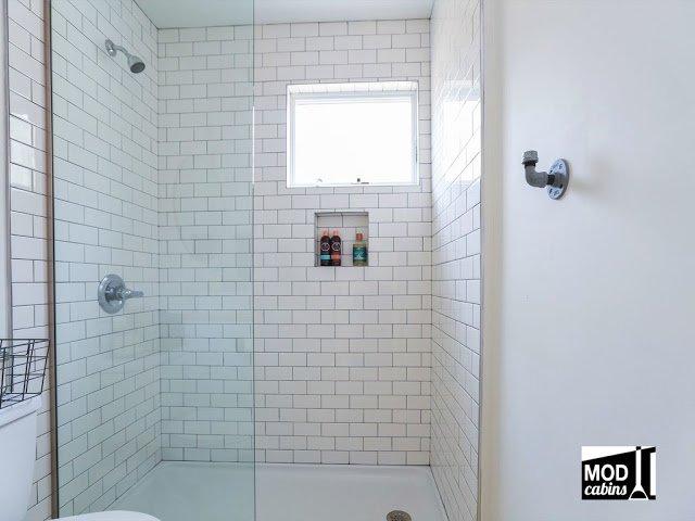 Просторная душевая обложена белым кафелем. В стене предусмотрена ниша для шампуней.