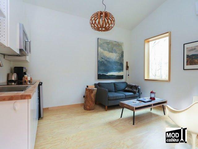 Высокие потолки жилой комнаты визуально увеличивают ее в размерах, как и белые стены.