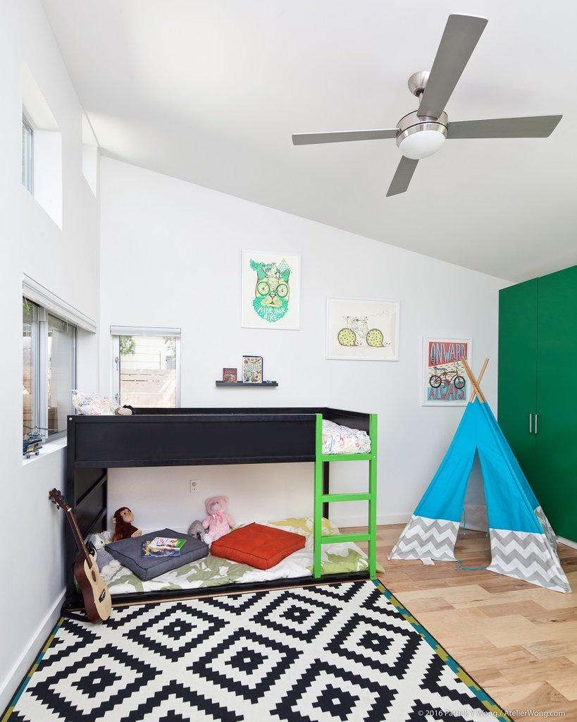 Детская с высоким наклонным потолком и высоко расположенными окнами.