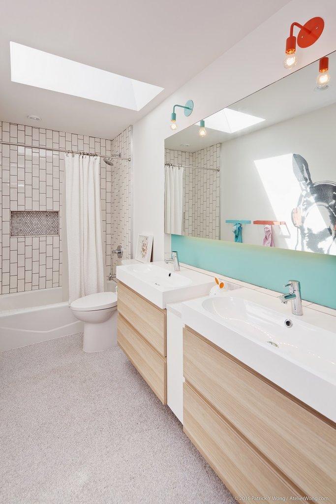 Детская ванная комната с мансардным окном в потолке и яркими акцентами подчеркивающими то что это детская ванна.