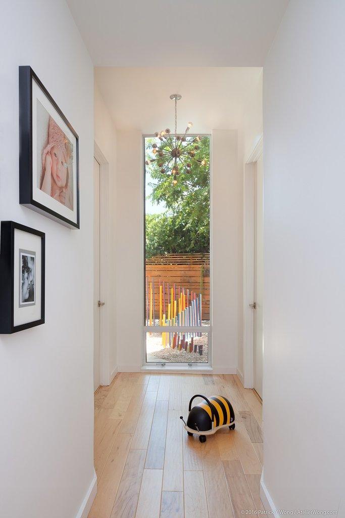 Коридор к спальням светлый оканчивающийся высоким окном от пола до потолка. Окно выходит в небольшой садик.