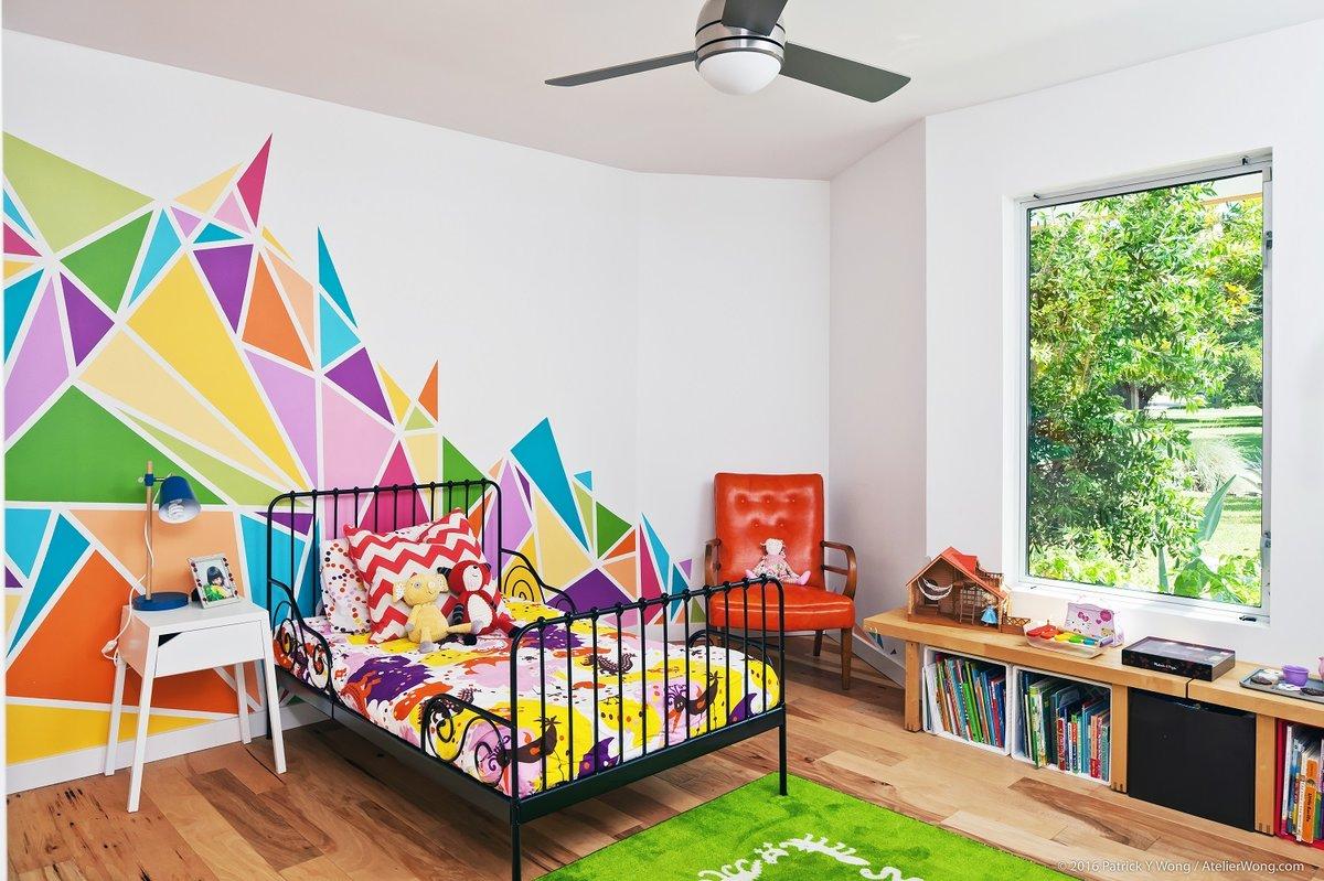 Подростковая детская комната с ярко раскрашенной  одной из стен. Подоконники низких окон заменены книжными стеллажами. На них можно даже посидеть.