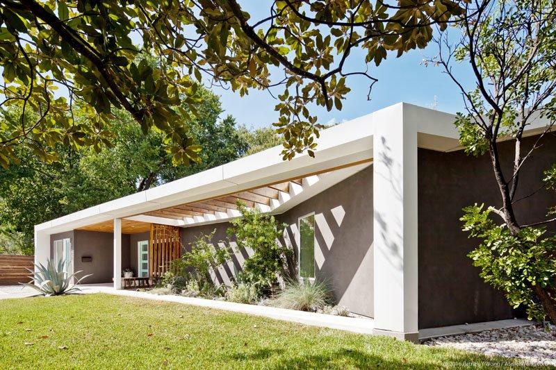 Совершенно новый передний фасад дома украшают зеленые растения.