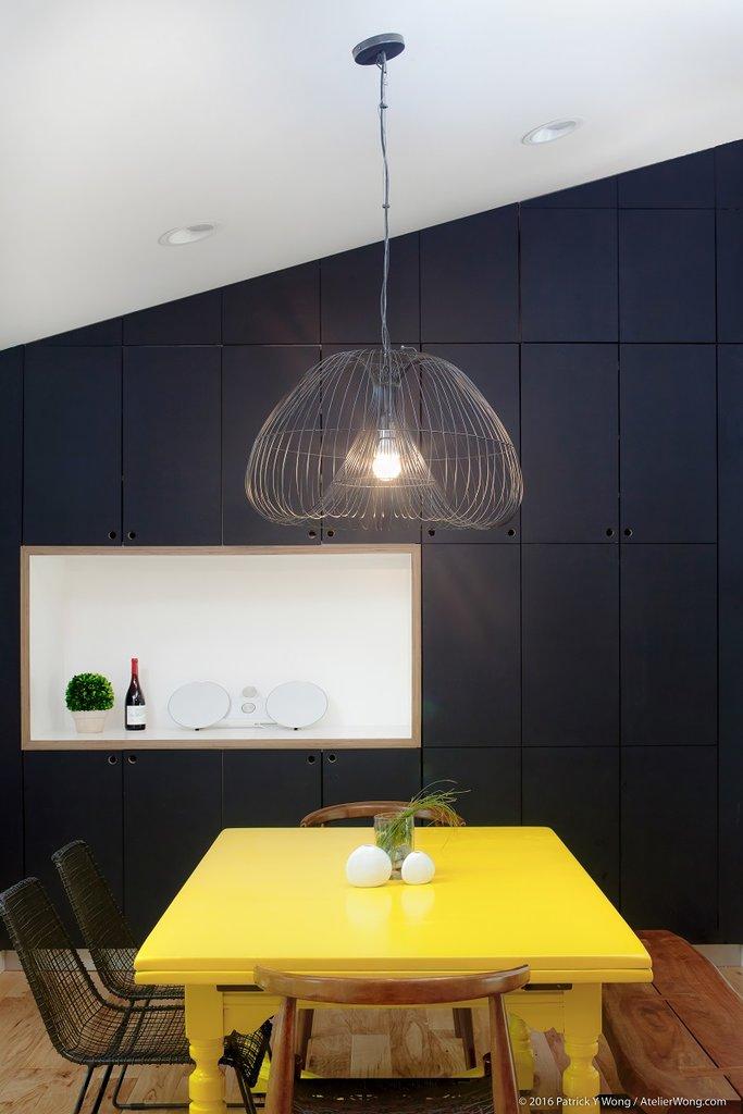 Желтый стол обозначает столовую в жилой комнате. Необычная люстра с проволочным плафоном освещает стол.