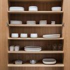 Не глубокий шкаф с полками для хранения посуды спрятан в стене рядом с кухней.