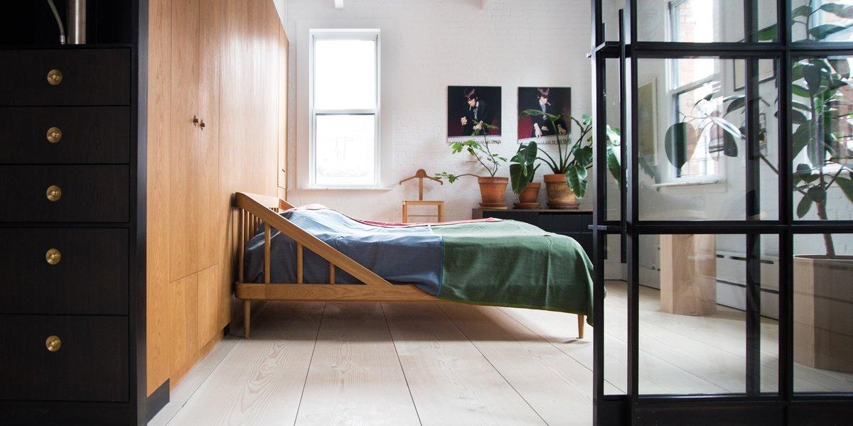 Деревянная кровать с необычным, но весьма привлекательным изголовьем. Целую стену спальни занимает система хранения с деревянным фасадом.