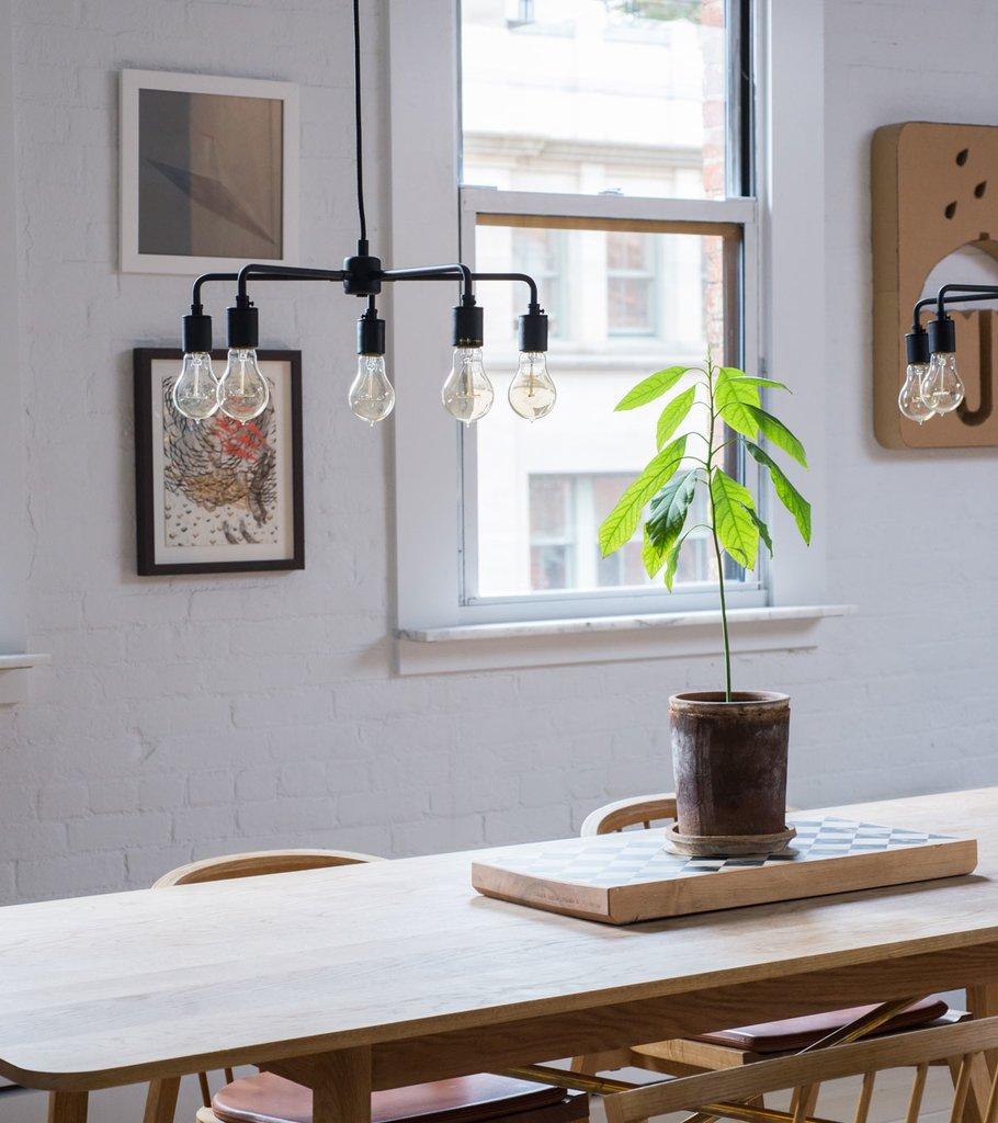Светильники без абажуров встречаются по всей квартире. Тут они освещают обеденный стол в столовой.