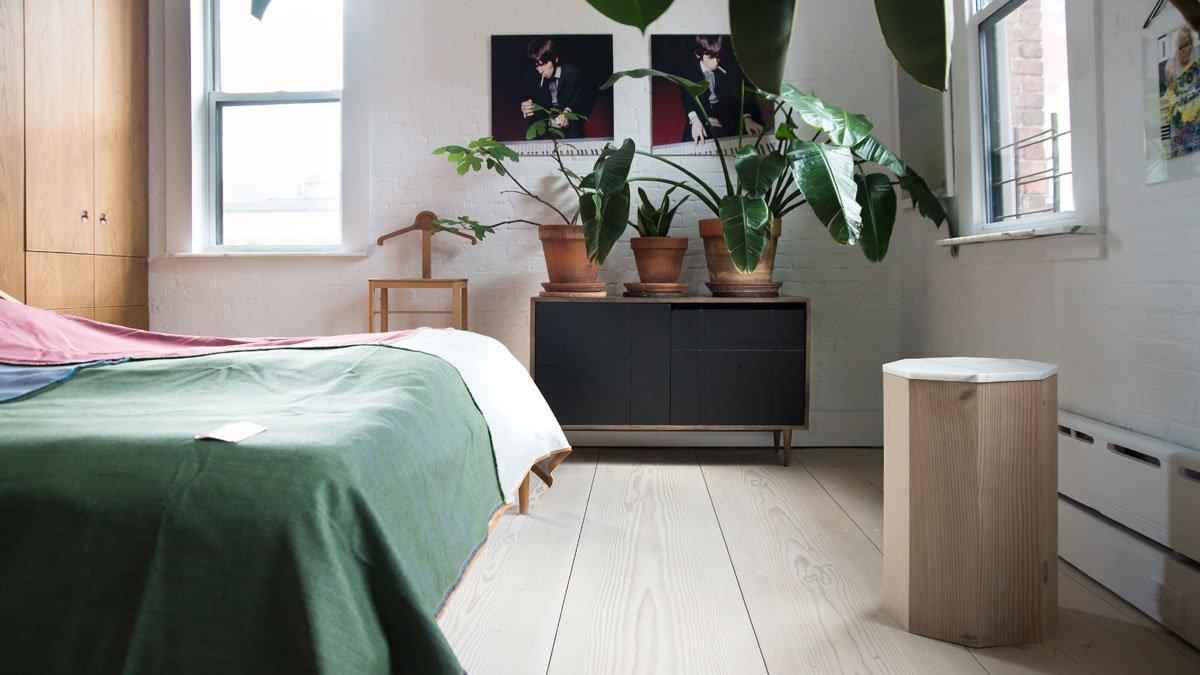 Зеленое покрывало гармонирует с зеленью цветов в спальне. В остальном доминируют разные оттенки натурального дерева.