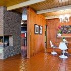 Центром гостиной служит угловой камин за которым находится кухня с барной стойкой..
