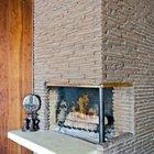 Элегантный угловой камин обложенный узкими камнями похожими на туф. Рядом с камином деревянная африканская фигурка.