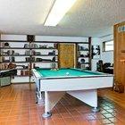 Игровая комната в цокольном этаже. В центре стоит бильярдный стол, вдоль всей дальней стены расположены книжные полки.