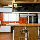 Красная кафельная плитка оживляет кухню. Над барной стойкой в воздухе висит остекленная с двух сторон темным стеклом полка для посуды.