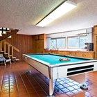 Стены игровой комнаты отделаны деревом, а пол практичной коричневой кафельной плиткой.