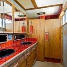 Ванная комната рядом с главной спальней. Столешница отделана красным кафелем, как и на кухне. Окно в верхней части хорошо освещает помещение. Душ отделен от ванной комнаты деревянной дверью. (1950-70е,середина 20-го века,медисенчери,медисенчери модерн,модерн,средневекоый модерн,модернизм,mcm,архитектура,дизайн,экстерьер,интерьер,дизайн интерьера,мебель,ванна,санузел,душ,туалет,дизайн ванной,интерьер ванной,сантехника,кафель,керамика,фото ванной,идеи ванной)
