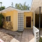 Вход в дом украшен решетчатыми бетонными блоками - стеной и забором. Рядом с входом расположена крытая парковка на пару машин.