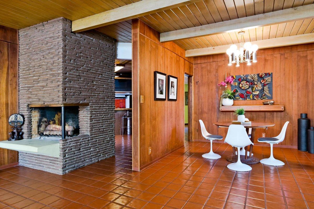 Центром гостиной служит угловой камин за которым находится кухня с барной стойкой