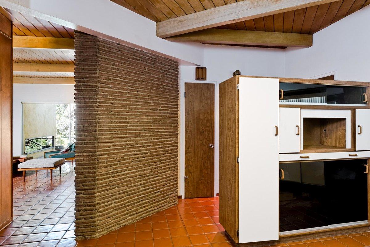 Камин отделяет гостиную от кухни. При этом между комнатами нет дверей.