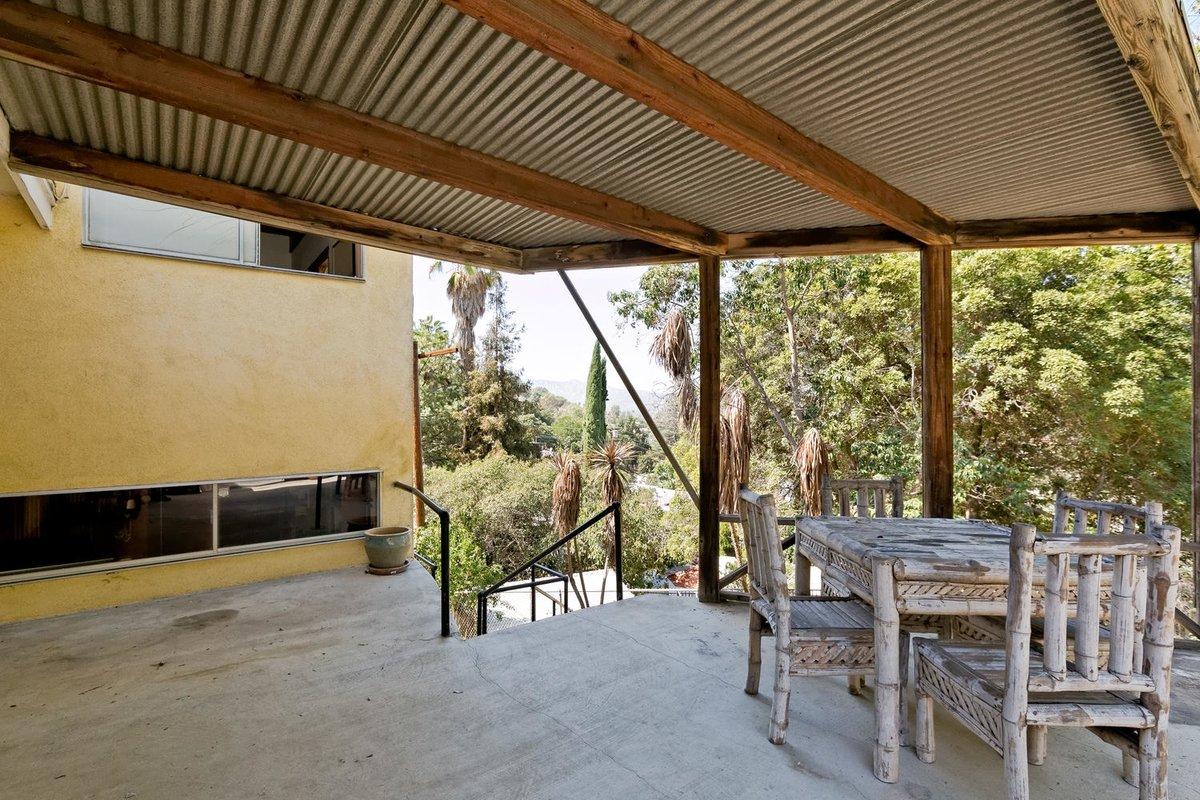 Крытая терраса рядом с гостиной находится выше уровня земли, что благоприятно влияет на вид открывающийся с террасы