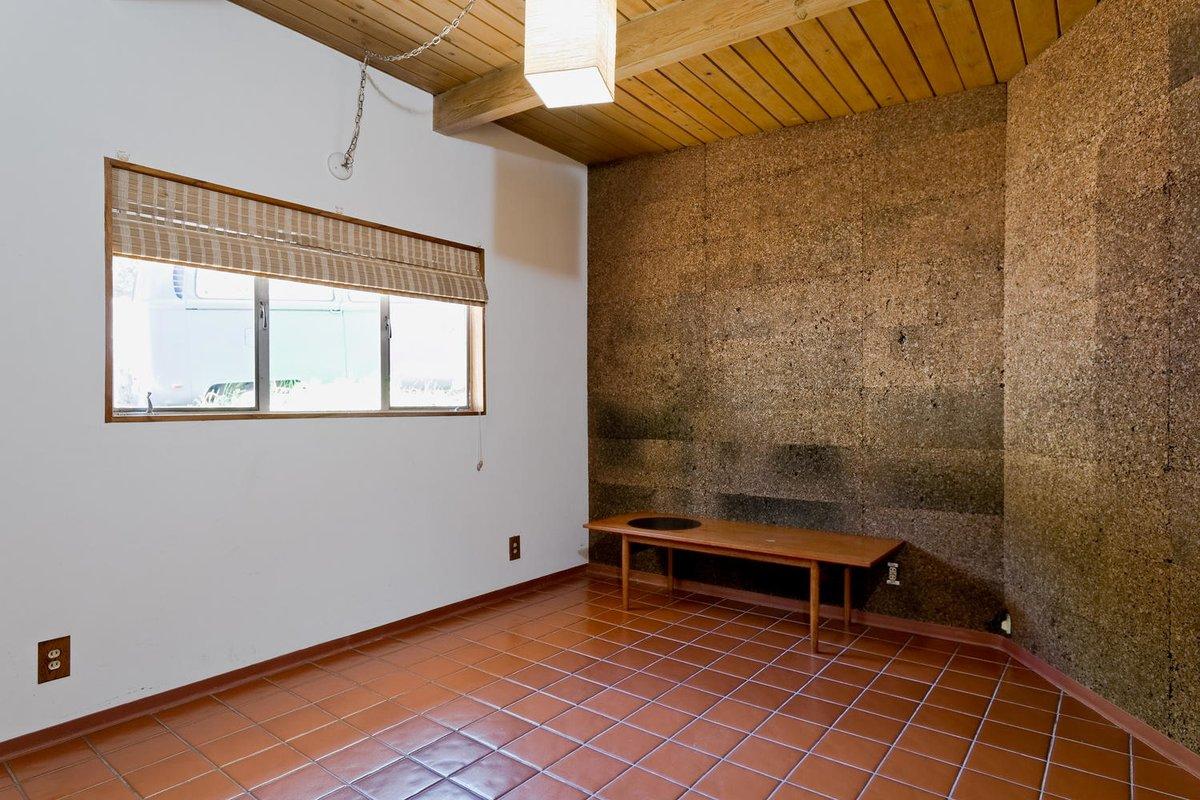 Одна из спален неправильной формы с отделкой стен пробкой.