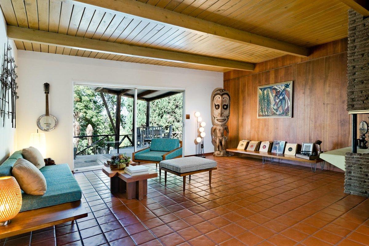 В углу комнаты примостился деревянный истукан рядом с которым на скамье огромная коллекция грампластинок и проигрыватель.