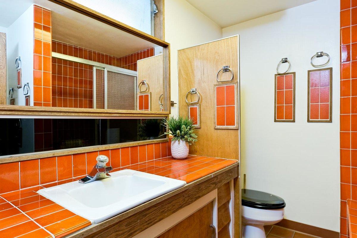 Ванная комната рядом с одной из спален украшена красным кафелем, как и кухня.