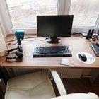 Небольшое, но удобное рабочее место у окна с белым кожаным креслом.