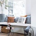 Низкий толстый подоконник-скамья со множеством подушек и журнальным столиком рядом с ним.