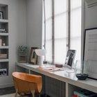 Рабочий стол на подоконнике протянувшемся от стены до стены. Под подоконником удобные полки для книг и принадлежностей.