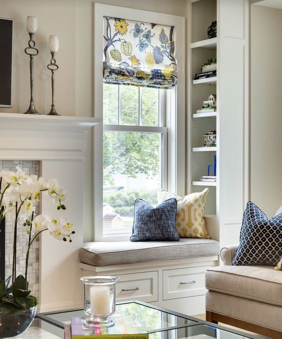 Небольшой подоконник с подушкой и вместительным стеллажом для книг.