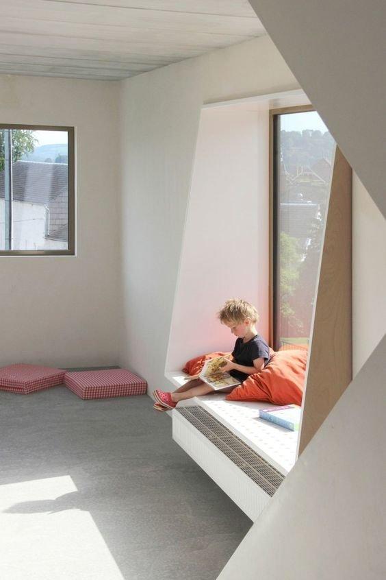 Низкий подоконник с подушкой в детской удобен для чтения и игр.