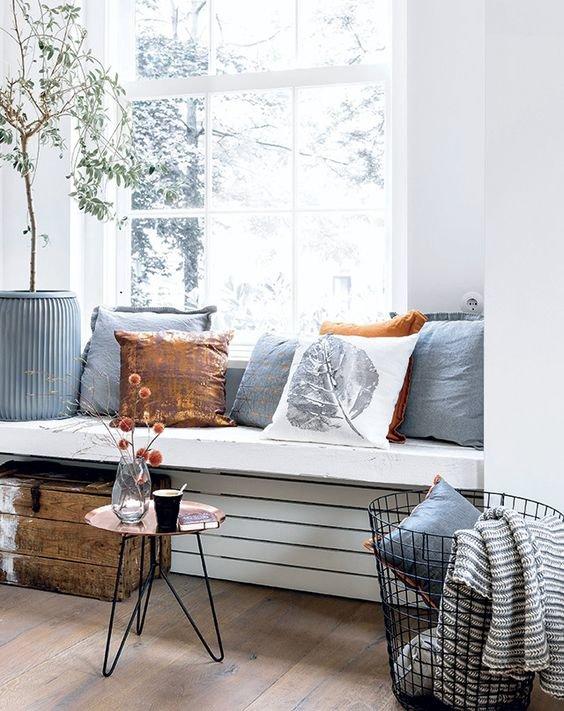 Низкий толстый подоконник-скамья со множеством подушек и журнальным столиком рядом с ним