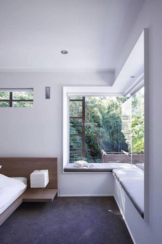 Удобный мягкий подоконник вдоль углового окна в спальне позволяет наслаждаться видами