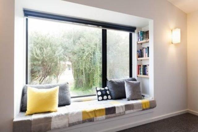 Удобный широкий подоконник у большого окна с книжными полками в одном из оконных откосов.