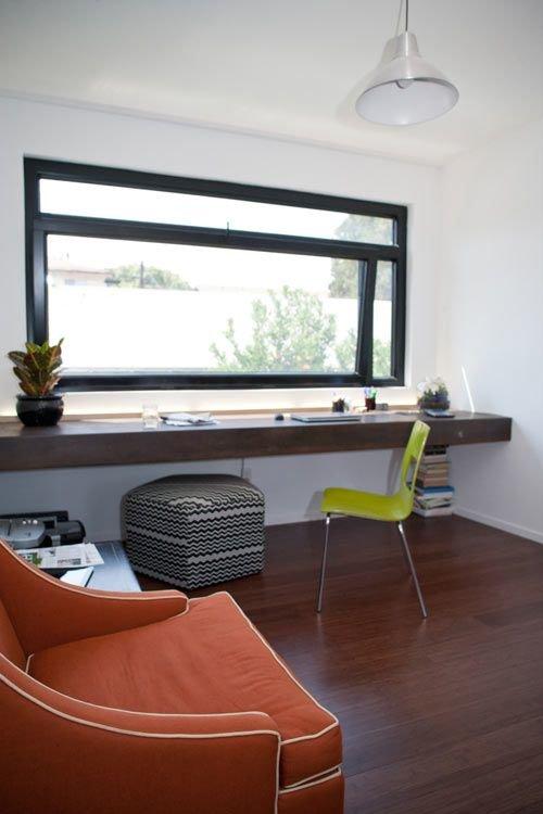 Великолепный домашний офис с рабочим столом-подоконником вдоль всей стены с современным стулом и пуфом.