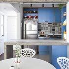 Бетонная барная стойка и холодильник из нержавейки отлично сочетаются с монохромной кафельной плиткой кухонного фартука и оттеняется голубым кухонным фасадом.