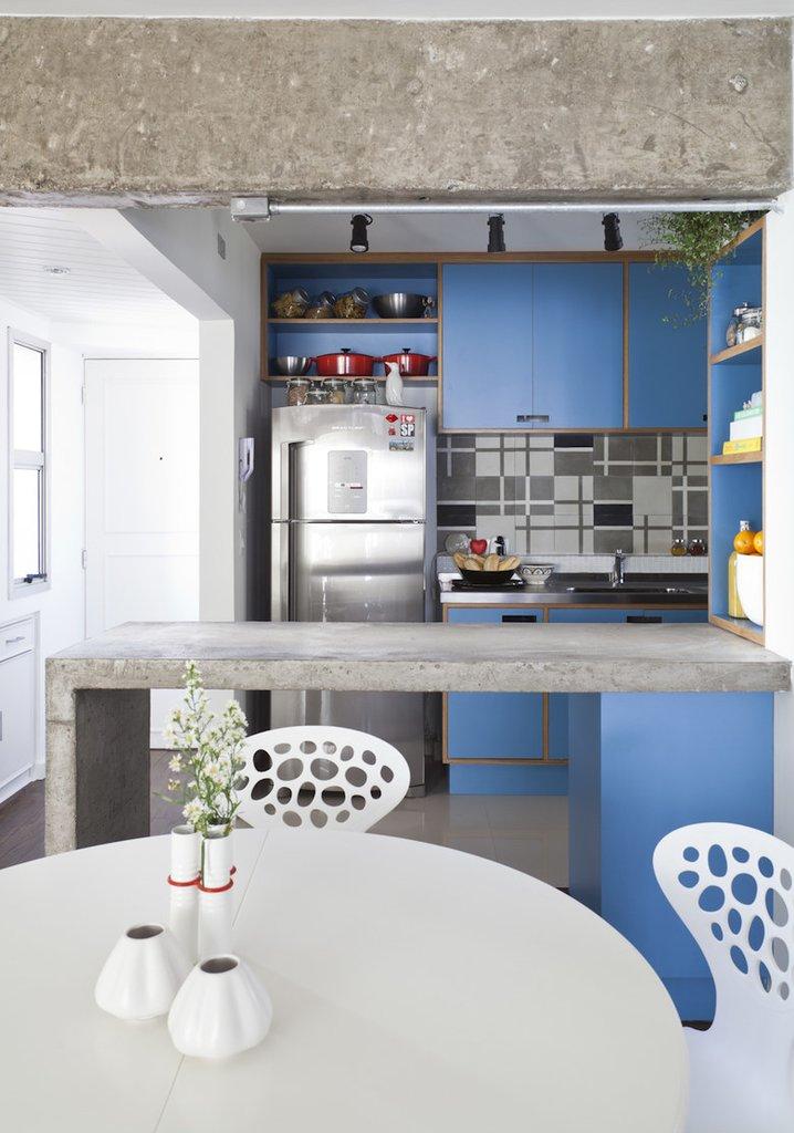 Бетонная барная стойка и холодильник из нержавейки отлично сочетаются с монохромной кафельной плиткой кухонного фартука и оттеняется голубым кухонным фасадом