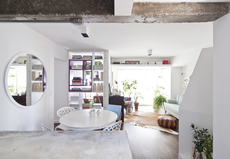 Бетонные балки, кирпичные стены, прозрачный стеллаж и круглое зеркало делают интерьер квартиры значительно интереснее, как и полка под потолком в гостиной.